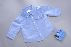 Single blue infant long sleeve shirt and toy Royalty Free Stock Photo