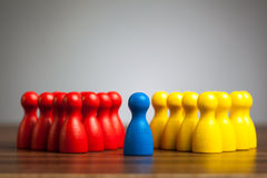 Single blue pawn figure between red and yellow groups. Blue figure in the middle between red and yellow groups. Meditation, leadership, diversity, unification stock photo