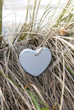 Single blue wooden heart on beach dunes royalty free stock photo
