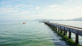 Single boat driving next to a pier Thailand Stock Photos