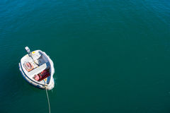 Single boat floating on blue-green sea Stock Photo