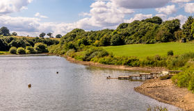 Single Boat by the Reservoir. Single fishing boat located on the shore, and next to a pontoon, of a huge reservoir. Supplying water to areas of Somerset and Stock Photo