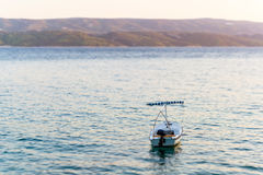Single boat in sea, visible mountains and island coast. Royalty Free Stock Images