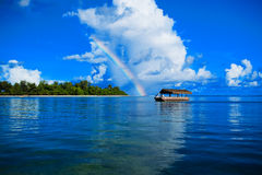 Single boat on the see under the rainbow Stock Photo
