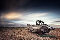 Single boat stranded on pebbled beach. Dungeness, England royalty free stock photos