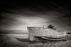 Single boat stranded on pebbled beach. Dungeness, England Royalty Free Stock Image