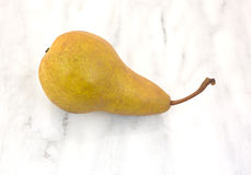 Single Bosc Pear On Marble Stock Photo