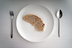 Single Bread served on white table in a gloomy mood Royalty Free Stock Photography