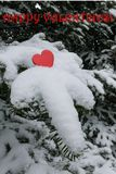 Single bright red Valentines heart on a snow laden Balsam fir tree branch with a Happy Valentines greeting.  Royalty Free Stock Image
