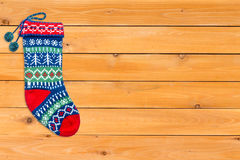 Single brightly colored woollen Christmas stocking. Single brightly colored empty woolen Christmas stocking waiting for Father Christmas arranged neatly to the Stock Photo