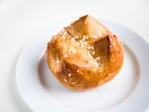 Single brioche, French bun on a white plate and background. Horizontal view from above of a single brioche, French bun, on a white plate and background stock image