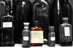 A single brown poison bottle on a shelf with other bottles Stock Image