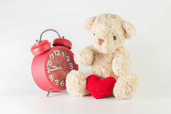 Single brown teddy bear with red heart yarn and alarm clock. Single brown teddy bear with red heart yarn and alarm clock on white background Royalty Free Stock Photos
