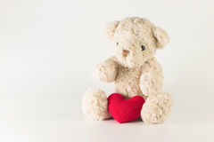 Single brown teddy bear with red heart yarn. Single brown teddy bear with red heart yarn on white background Royalty Free Stock Images