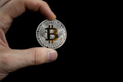 Single BTC Bitcoin coin in hand Royalty Free Stock Images