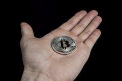 Single BTC Bitcoin coin on hand Stock Photos