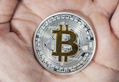 Single BTC Bitcoin coin on hand Stock Image