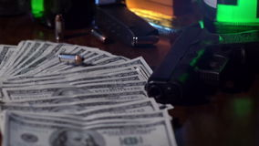 Single bullet fall onto pile of money in slow motion. True crime or film noir style shot of a bullet dropping in slow motion onto a pile of money. A gun lies to stock video