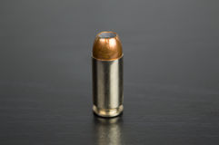 Single bullet for a gun on a black table Stock Image