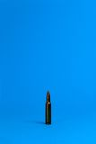 A single bullet. Is standing on a blue ground Royalty Free Stock Image