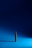 A single bullet. Is standing on a blue ground Royalty Free Stock Photo