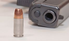 A single bullet on a white table with a black pistol in the background. A single 9mm hollow point bullet on a white table in front of a black pistoln Stock Photos