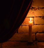 Single burning candle. On velvet curtain background Royalty Free Stock Photography