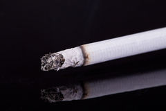 Single burning cigarette with ash isolated on black background Royalty Free Stock Photos
