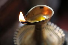Single burning flame in a brass oil lamp. On a dark Background Stock Images