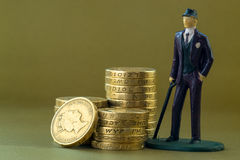 Single Business Man Miniature Model and English One Pound Coins Royalty Free Stock Photo