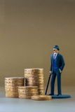Single Business Man Miniature Model and English One Pound Coins Stock Photography