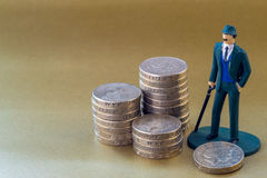 Single Business Man Miniature Toy and English One Pound Coins Stock Photo