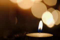 Single candle with beautiful diagonal bokeh. Single candle burning in darkness against a diagonal line of lights Royalty Free Stock Images