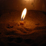 Single candle burning Stock Images