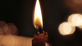 Single candle with flame fire dripping wax in stock footage