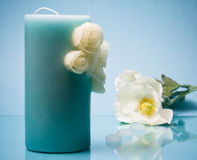 Single candle and flowers on blue Stock Images