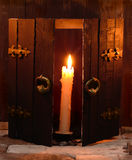 Single candle and open door. Burning candle and aged open gates in background Royalty Free Stock Images