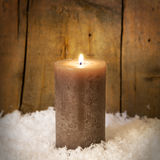 A single candle in snow Royalty Free Stock Image