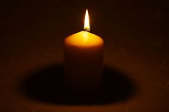 Single candle on tablecloth Stock Images