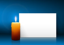 Single Candle with White Paper Panel on Blue Background Royalty Free Stock Image