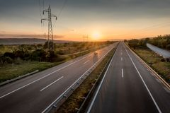 Single Car at a Beautiful Motorway at sunset. Single Car at a Beautiful Silent Countryside Motorway and power line at sunset royalty free stock photos