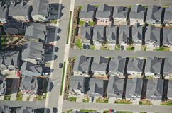 Single Car Driving Out of Housing Complex. Aerial view of rows of houses and a commuter car heading to work Stock Photography