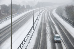 Single Car On Motorway During Snow Storm Stock Photo