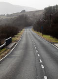 Single carriageway road into distance Stock Photos