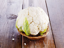 Single cauliflower on rustic wooden background. Single head of cauliflower in a straw basket on a rustic wooden background stock images