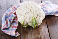 Single cauliflower on wooden background. Single head of cauliflower on a rustic wooden background stock photos