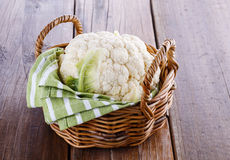 Single cauliflower on woven basket on wooden background Stock Image