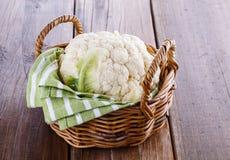 Single cauliflower on woven basket on wooden background. Single head of cauliflower in a woven basket on a rustic wooden background stock image