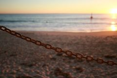 Single chain link against an out of focus beach sunset in the background. Single chain against an out of focus beach sunset in the background royalty free stock photos