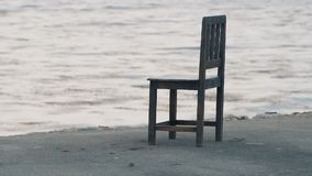 Single chair at the seafront. Sea waves moving slowly stock video